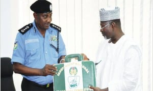 INEC Chairman Prof. Attahiru Jega (right), presenting  INEC bag to the Acting IG, Mr Solomon Arase, during his first visit to INEC headquarters in Abuja, last Friday