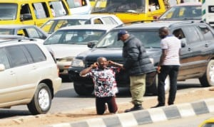 A man being punished by a  law enforcement  officer for not using Pedestrian Bridge in Ikeja, Lagos, yesterday