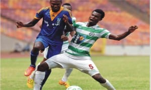 Dolphins FC's player (5) trying to stop an opponent in a 2015 Glo Premier League encounter at the Liberation Stadium, Port Harcourt, recently.