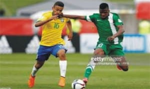 Flying Eagles' Kelechi Iheanacho (right) in a  tussle with a Brazilian opponent on Monday.