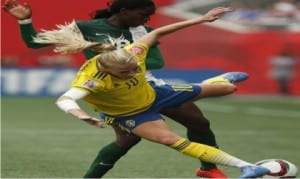 Sweden's Sofia Jakobsson (10) knocked off the ball by Nigeria's Asisat Oshoala (8) during the first half of a FIFA Women's World Cup soccer match in Winnipeg, Manitoba, Monday, June 8, 2015.