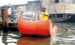 A pupil  paddling himself in an improvised canoe to School at Makoko Community in Lagos State, recently.