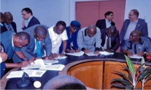 Gov. Nyesom Wike (extreme right) watch representatives of 7 companies sign MoU with the state government and RCC Nigeria Limited in the emergency repair of KM0-15 East/West Road phase 3  at Indoroma conference hall, Eleme.