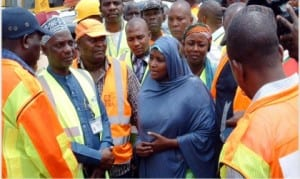Permanent Secretary, Federal Ministry of Aviation, Hajia Binta Bello (middle), speaking with the rescue team at the scene of Wednesday's crashed helicopter, as two more bodies were recovered at Oworoshoki in Lagos, yesterday