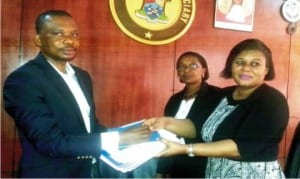 Executive-Director, Centre for Citizens with Disabilities, Mr David Anyaele (left), presenting a research report on access to justice and persons with disabilities to representative of the Chief Judge, Ikeja High Court, Mrs Funmi Ajayi (right) in Lagos on Friday. With them is the Deputy Registrar, Mrs Judith Momodu.