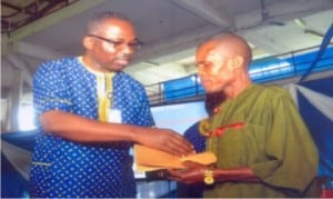 Head of Service,  Rivers State,  Barrister Rufus Godwins (left), presenting a Merit Award to a civil servant in the office of the  Head of Service,  Mr. George Geoffrey, during  Civil Service Week celebration in Port Harcourt, yesterday         Photo: Chris Monyanaga