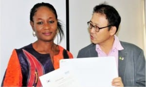 Country Director, Korea International Cooperation Agency in Nigeria (KOICA), Mr Jung Sang-Hoon (right), presenting an award to Bimbola Owojaiye, one of the champion students selected in e-Government Pilot Training under the auspices of KOICA,  in Abuja, last Friday