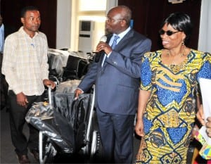 Permanent Secretary,  Ministry of Women Affairs and Social Development,   Dr Ezekiel Oyemomi (left), presenting a wheel chair  to the Coordinator, Congenital   Deformity Babies Foundation, Kaduna, Mr Innocent Uche, on behalf of the foundation  in Abuja, recently.  With them is the Director, Rehabilitation, Ms  Victoria Akintaro.