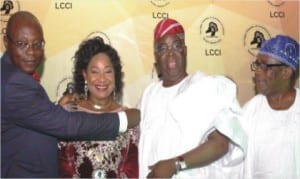 Out-going President, Lagos Chamber of Commerce and Industry (LCCI), Alhaji Remi Bello (left), decorating the incoming president of the Chamber, Dr Nike Akande (2nd right) in Lagos, yesterday. With them are her husband,Chief Adebayo Akande (2nd right) and former President of LCCI,Chief John Odeyemi.