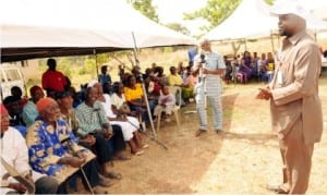 Representative of Project Director Naca/Sure-p, Dr Chukwugozie Ujam (right), addressing beneficiaries of NACA/SURE-P's free  medical outreach at Akpasha Nkanu community in Enugu State on Monday