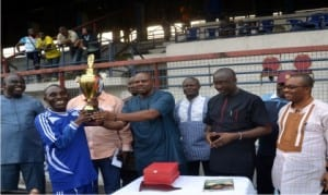 General Manager, Rivers State Newspaper Corporation, Mr Celestine Ogolo (right) and other dignitries look on as Rivers State Commissioner for Sports, Hon Boma Iyaye (4th left) presents the maiden Rivers SWAN Henry Kalio Cup to the captain of The Tide/Independent Monitor team, Isaac Mbah after the final match of the competition in Port Harcourt, yesterday