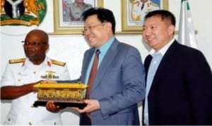 Chief of Naval Staff, Vice Admiral Ibok-ete Ibas (left), receiving a souvenir from the Chairman, Beijing Jiany Investment Group, Mr Zhang Ming (middle), during their visit to Naval headquarters in Abuja on Monday . With them is the Manager, Beijing Jiany Investment Group, Mr Li Shuo.