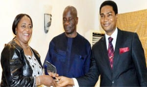 Representative of the Minister of Foreign Affairs, Mr Akinyemi Bolaji (right), presenting an award to Nigeria's former High Commissioner to the Gambia, Amb. Esther Audu, in recognition of building a robust bilateral relations between Nigeria and Gambia, during the first Edition of Diplomatic Correspondents Association of Nigeria (DICAN's) Diplomatic awards night in Abuja  on Wednesday. With them is the envoy's spouse, Mr John Audu.