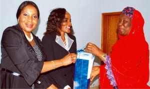 Representative of the Acting Managing Director, News Agency of Nigeria (nan), Hajiya Kahdijat Lawal (right), presenting a souvenir to  the  National Publicity Secretary, International Federation of  Women Lawyers (fida), Princess Frank-Chukwani (left) and the fida National Secretary, Mrs Rhoda Tyoden-Moore, during the visit of fida delegation to nan headquarters in Abuja, recently.