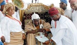 Governor Abiola Ajimobi of Oyo State (right), presenting certificate to the new Olubadan of Ibadan, Oba Saliu Adetunji, during the Oba's coronation in Ibadan on Friday . With them is the Oba's eldest wife, Alhaja Rafiat Adetunji.