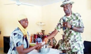 goc, 7th Division of the Nigerian Army Maiduguri, Brig.-Gen. Victor Ezugwu (right) presenting cash to a beneficiary of soft loans to unemployed youths and women groups under the Chief of Army Staff Empowerment Initiatives to barracks community in Maiduguri on Sunday.