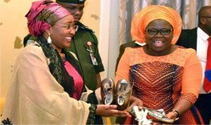 Wife of the  President, Mrs Aisha  Buhari (left) receiving Aba made-in-Nigeria products  from  wife of the Governor of Abia State,  Mrs Nkechi  Ikpeazu,  during a courtesy call on the wife of the president by Abia State women in Abuja on Wednesday.