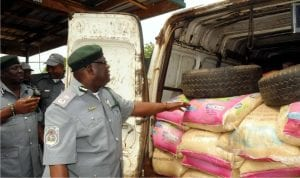 Customs Area Comptroller Oyo/Osun Area Command, Mr Temitope Ogunkua showing newsmen some bags of  rice seized from smugglers in Ibadan, recently