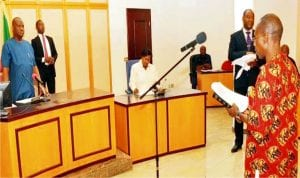 Governor Nyesom Wike of Rivers (left) Swearing-in-Commissioner of  Rivers Independent Electoral Commission, (RSIEC), Mr Ugbana  Isaruk in Port Harcourt, recently.