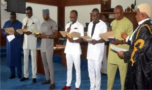 Clerk of the Rivers State House of Assembly, Mr Stanford Oba (right), swearing-in the newly elected members of the Rivers State House of Assembly, yesterday