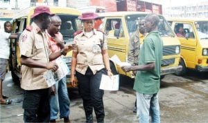 Surulere Unit Commander of the Federal Road Safety Corps, Mr Tunji Oguntonye (left), discusing with commercial bus drivers on the need to obey speed limit at Ojuelegba, during the West African Safety Organisation Day celebration in Lagos, recently.